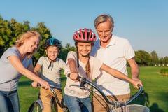 Nonni che aiutano la bicicletta di giro dei bambini Immagini Stock