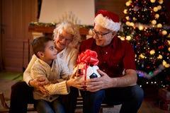 Nonni che danno il nipote dei regali alla notte di Natale immagine stock libera da diritti
