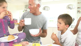Nonni con i nipoti che mangiano prima colazione in cucina video d archivio