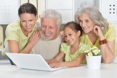 Nonni, derivato e nipote che per mezzo del computer portatile Fotografia Stock