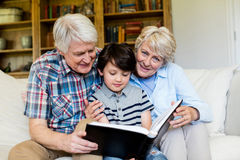 Nonni e nipote che esaminano album di foto in salone Immagine Stock Libera da Diritti