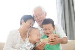 Nonni e nipoti che prendono selfie facendo uso degli Smart Phone Fotografia Stock Libera da Diritti