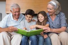 Nonni felici e grandkids che esaminano la foto dell'album fotografia stock libera da diritti