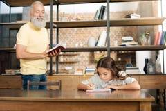 Nonno allegro che detta le parole alla sua nipote Fotografie Stock