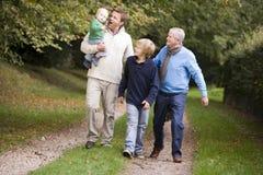 Nonno che cammina con il figlio ed i nipoti Immagini Stock