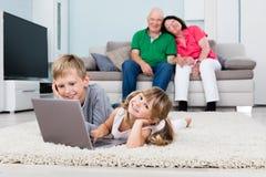 Nonno che esamina i loro nipoti che per mezzo del computer portatile Fotografia Stock
