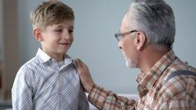 Nonno che esprime parere al ragazzo, più giovane generazione d'istruzione, condividente esperienza fotografia stock