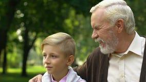Nonno che mostra al suo nipote qualcosa nel parco, godente insieme del tempo libero stock footage