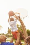 Nonno con il figlio ed il nipote che giocano pallacanestro Immagini Stock