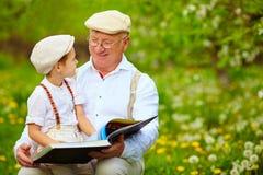 Nonno con il libro di lettura del nipote nel giardino di primavera Fotografia Stock Libera da Diritti