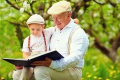 Nonno con il libro di lettura del nipote nel giardino di primavera Immagine Stock