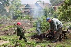 Nonno con il nipote che prepara barbecue Fotografia Stock Libera da Diritti