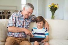 Nonno con il suo nipote che per mezzo della compressa digitale sul sofà Fotografia Stock