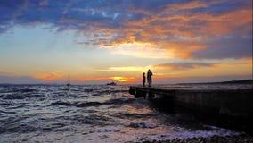 Nonno con la nipote nel tramonto in mare, siluette soltanto, non riconoscibile archivi video