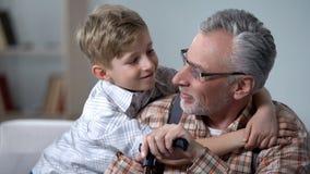 Nonno d'abbraccio del nipote con amore, minuti preziosi della famiglia, cura anziana fotografia stock libera da diritti