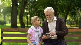 Nonno d'istruzione del ragazzo per utilizzare smartphone, nuove tecnologie difficili per il pensionato archivi video
