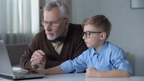 A nonno del bambino mostrando come cercare informazioni in Internet facendo uso del computer portatile video d archivio