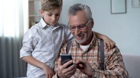 Nonno di spiegazione del nipote come utilizzare smartphone, app facile per gli anziani fotografia stock