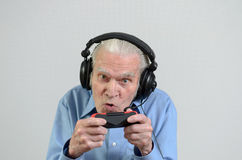 Nonno divertente che gioca un video gioco sulla console Fotografia Stock