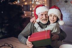 Nonno e nipote in cappelli del ` s di Santa Claus alla notte a casa Il nonno sta dando il ragazzo presente fotografia stock libera da diritti