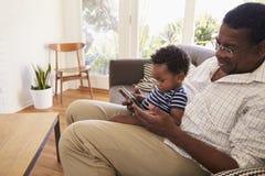 Nonno e nipote a casa facendo uso della compressa di Digital Fotografie Stock Libere da Diritti