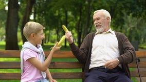Nonno e nipote che giocano i moschettieri, banane combattenti, gioco divertente, scherzo video d archivio