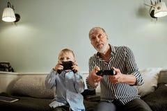 Nonno e nipote che giocano i video giochi sul computer con la leva di comando immagini stock