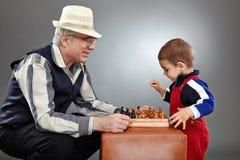 Nonno e nipote che giocano scacchi Fotografie Stock Libere da Diritti