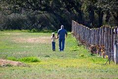 Nonno e nipote che parlano nel pascolo Fotografie Stock Libere da Diritti