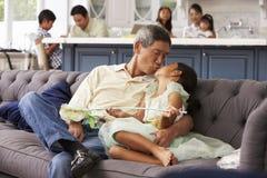 Nonno e nipote che si rilassano su Sofa At Home fotografia stock