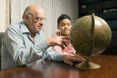 Nonno e nipote che si siedono alla tabella con il glo Fotografia Stock