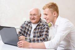 Nonno e nipote che si siedono con il computer portatile Immagini Stock Libere da Diritti