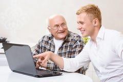 Nonno e nipote che si siedono con il computer portatile Fotografia Stock