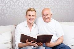 Nonno e nipote che si siedono con l'album Fotografia Stock