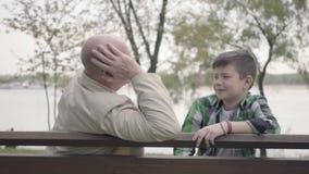 Nonno e nipote che si siedono nel parco vicino al fiume sul banco, uomo anziano che racconta storia interessante al ragazzo archivi video