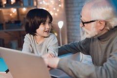 Nonno e nipote che si siedono sul computer portatile alla notte a casa immagini stock libere da diritti