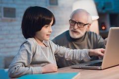 Nonno e nipote che si siedono sul computer portatile alla notte a casa fotografia stock libera da diritti