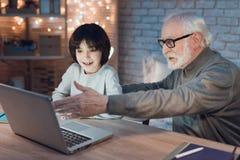 Nonno e nipote che si siedono sul computer portatile alla notte a casa fotografie stock libere da diritti