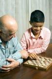 Nonno e nipote che si siedono sul gioco della tabella Immagini Stock Libere da Diritti