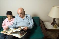 Nonno e nipote che si siedono sullo strato colto Immagini Stock