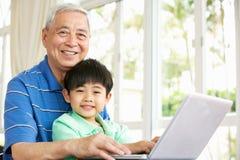 Nonno e nipote cinesi che per mezzo del computer portatile Fotografia Stock