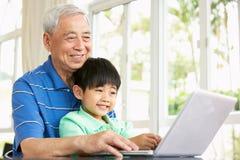 Nonno e nipote cinesi che per mezzo di un computer portatile Fotografia Stock Libera da Diritti