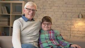 Nonno e nipote con i vetri, sedendosi sullo strato, sorridendo ed esaminando la macchina fotografica Comodità domestica, famiglia video d archivio