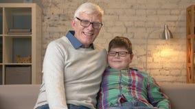 Nonno e nipote con i vetri, sedendosi sullo strato, sorridendo ed esaminando la macchina fotografica Comodità domestica, famiglia stock footage