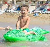 Nonno e nipote sorridenti che giocano e che spruzzano nell'acqua di mare Ritratto del ragazzo felice del bambino sulla spiaggia d immagini stock