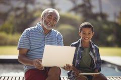 Nonno e nipote sorridenti che si siedono insieme sul banco con il computer portatile e la compressa digitale Fotografie Stock Libere da Diritti