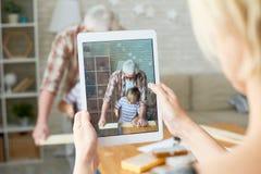 Nonno e nipote sullo schermo della compressa di Digital fotografia stock