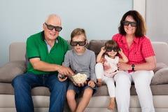 Nonno e nipoti che guardano film 3D Fotografia Stock Libera da Diritti