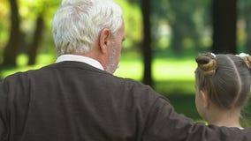 Nonno e storie dire, sedentesi sul banco in parco con i nipoti archivi video