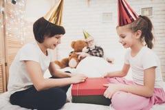 Nonno, nipote e nipote a casa I bambini stanno aprendo il presente mentre il nonno sta dormendo fotografie stock
